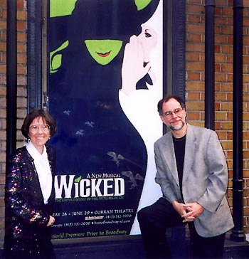 Carol and Gregory standing in front of the Curran Theatre with the Wicked poster